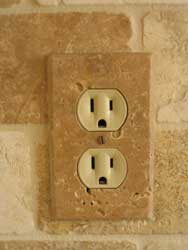 Installed travertine electrical outlet cover plate